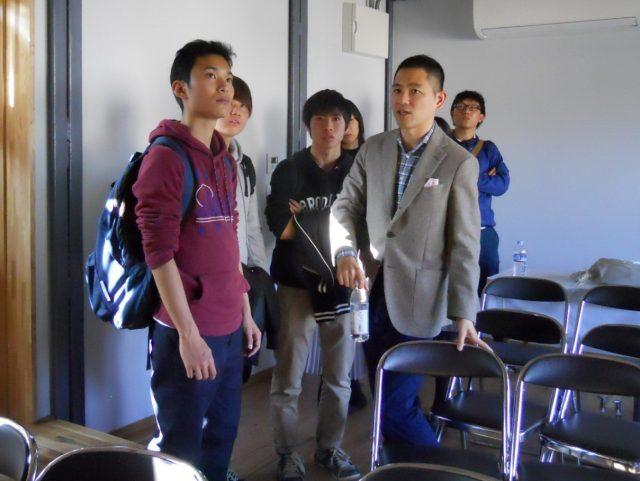 来場した学生から質問を受けるexpoの山根氏(右)
